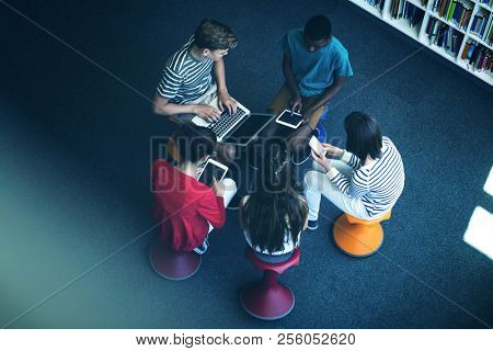Overhead view of students using laptop, mobile phone, digital tablet in library at school