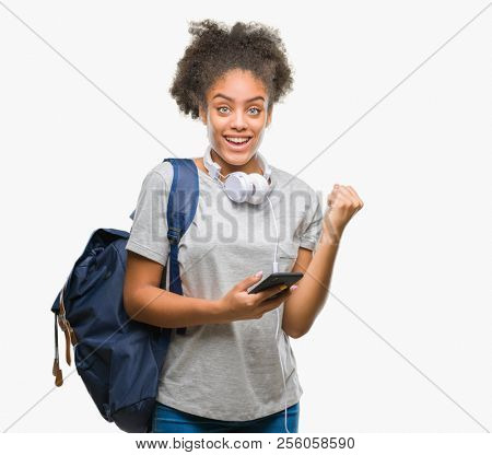 Young beautiful afro american student woman holding backpack over isolated background screaming proud and celebrating victory and success very excited, cheering emotion