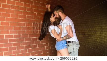 Girl And Hipster Full Of Desire Cuddling. Couple In Love Full Of Desire Brick Wall Background. No Ru