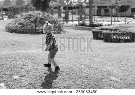 Happy Cute Baby Boy, Small, Little Child With Long Blond Hair In Blue Striped Clothes Playing On Gre