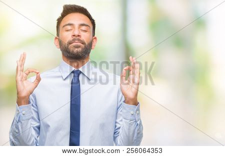 Adult hispanic business man over isolated background relax and smiling with eyes closed doing meditation gesture with fingers. Yoga concept.