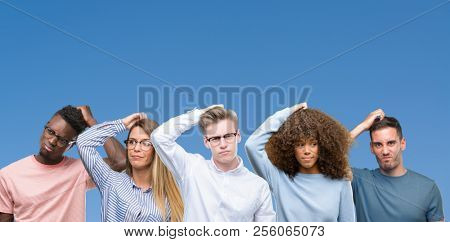 Composition of group of friends over blue blackground confuse and wonder about question. Uncertain with doubt, thinking with hand on head. Pensive concept.