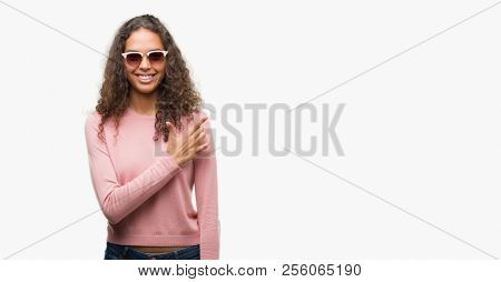 Beautiful young hispanic woman wearing sunglasses cheerful with a smile of face pointing with hand and finger up to the side with happy and natural expression on face looking at the camera.