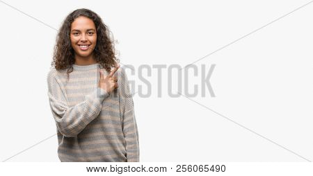 Beautiful young hispanic woman wearing stripes sweater cheerful with a smile of face pointing with hand and finger up to the side with happy and natural expression on face looking at the camera.
