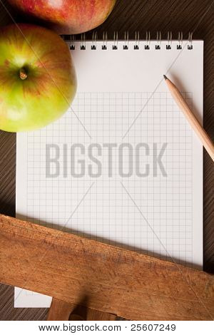Empty spiral notebook with apples on table