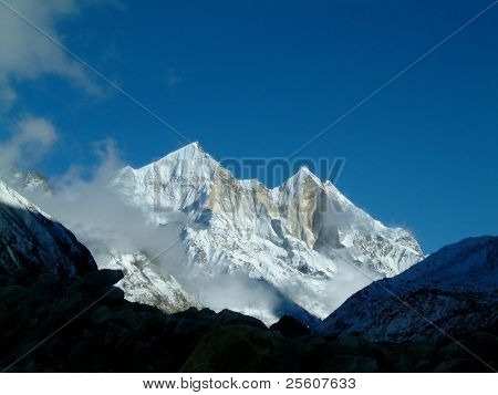 pristine view over mount bhagirathi, over 7700m high, few clouds floating about