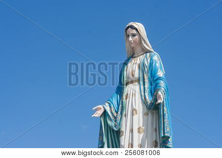 Blessed Virgin Mary Statue Or Sculpture  Place In Front Of The Roman Catholic Diocese With Blue Sky
