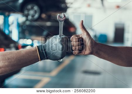 Close-up Thumb Up And Mechanics Hand With Tool. Automobile Master Wearing Gloves Showing Positive Ge