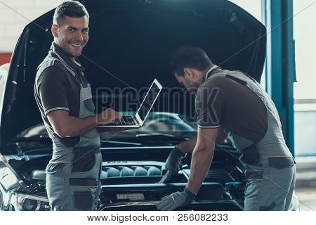 Two Car Mechanics Working In Auto Repair Service. Professional Caucasian Handsome Happy Workers In U