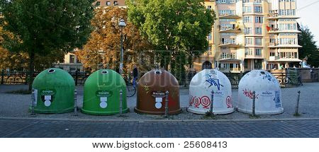 recycling containers lined up on a street in berlin, germany