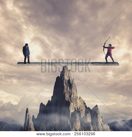 Archer Aim To Shoot A Weak Man On A Balance Above A Mountain. The Concept Of Karma.