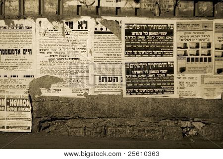 hasidic jews walking in front of propaganda panels, jerusalem, israel