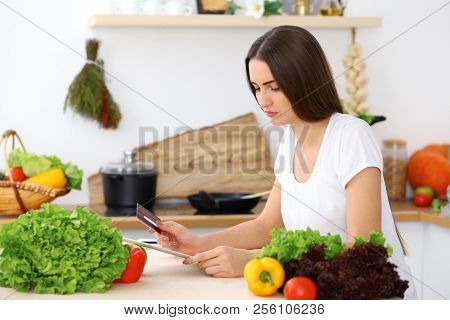 Beautiful Hispanic  Woman Cooking While Using Tablet Computer In Kitchen Or  Making Online Shopping