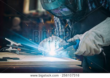 Strong Man Welder In Work Clothes Hard Working And Welds With A Welding Machine Metal   In The Works
