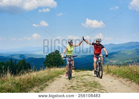 Happy Couple Bicyclists In Professional Sportswear And Helmets Riding Cross Country Bicycles On The