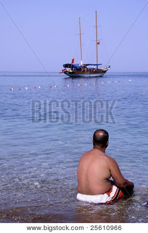 man sitting on beach with boat in background