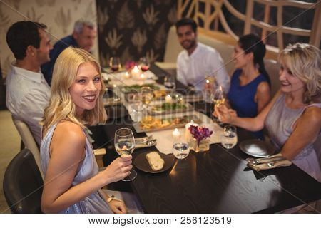 Portrait of smiling woman having champagne with their friends in restaurant
