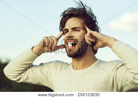 Guy hold dieting pill and vitamin. Man with pill in mouth outdoor on blue sky. Health and medicine. Drug and antidepressant. Treatment and hypnotic tablet. poster
