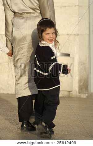 JERUSALEM - MAY 22 : Young orthodox Jew follows his father through old town Jerusalem May 22, 2007 in Jerusalem, Israel.
