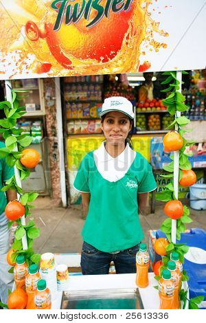 DELHI - FEBRUARY 26:  Hostess trying to promote artificial fruit juices in front of a traditional fresh fruit stall on February 26, 2008 in Delhi, India. This is where traditional meets modernity