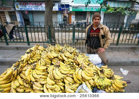 DELHI - JANUARY 18: Man selling bananas piled up on the street on January 18, 2008 in Delhi, India. Supermarkets are very rare so people buy from street stalls.