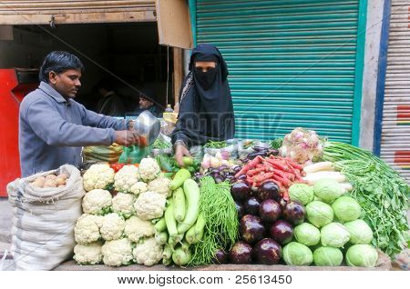 DELHI - JAN 15: Muslim woman with veil shopping vegetables on street stand on January 15, 2008 in Delhi, India. Supermarkets are rare and people mostly shop at street markets.