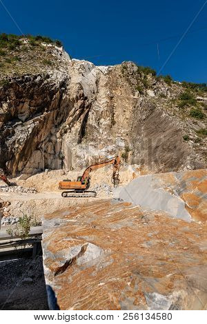 Orange tracked excavator with the jackhammer in a marble quarry (Carrara white marble) in the Apuan Alps (Alpi Apuane). Tuscany, (Toscana), Italy, Europe poster
