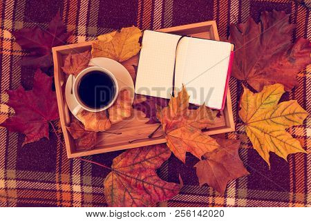 Cup Of Coffee, Opened Notebook And Autumn Leaves On Warm Brown Plaid. Top View.