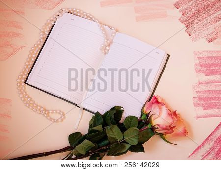 Pink Roses And Diary On Beige  Background. Top View.