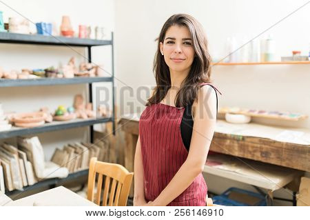 Portrait of confident female artisan wearing apron in pottery studio poster