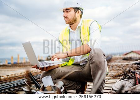 Dramatic View Of Civil Construction Engineer, Working With Laptop On Construction Site
