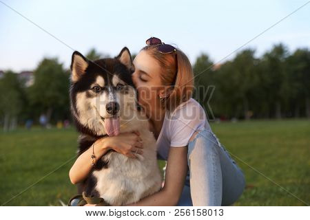 The Owner Of The Pet Hugs And Kisses Him. Beautiful Blonde Girl Walking Her Dog.