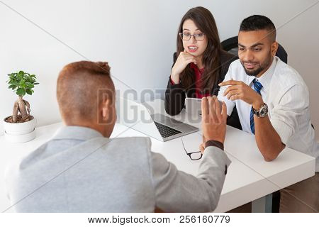 Manager Showing New Mobile App To Skeptical Colleagues. Two Office Employees Looking At Coworker Sma