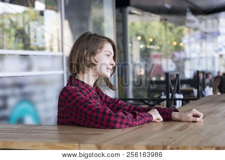 Portrait Of Beautiful Young Female Looking Away. Pretty Model Sitting In Cafe With Nice Interior. Pe