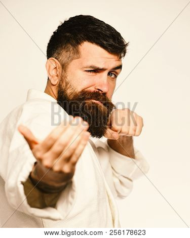 Taekwondo Master Practices Attack And Provokes Fight. Man With Beard In White Kimono On White Backgr