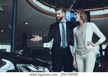 Car Salesman Showing Car To Woman In Showroom. Car Buying Deal. Beautiful Young Woman Talking To Cau