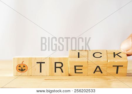 Halloween Trick Or Treat Concept, Hand Man Try To Flip Or Rotate The Wooden Dice To Change The Word