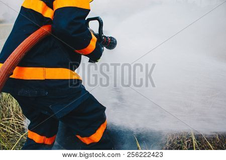 Firefighter Using Extinguisher And Water From Hose For Fire Fighting, Firefighter Spraying High Pres