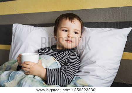 Sick Upset Cute Curing Boy Lying On Bed On Pillow Under Blanket Taking Medicament In Cup