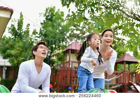 Family Concept. Family Is Doing Happy Activities At Playground. Parents With Children Are Playing In