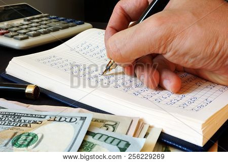 Bookkeeper Writing Financial Report Into The Bookkeeping Book.