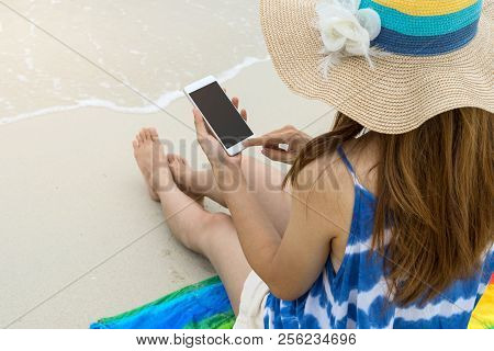 Young Woman Relaxing And Using Mobile Phone At The Tropical Beach, Summer Vacation And Travel Concep