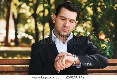 Serious Man Looking On His Watch. Handsome Guy In Suit Sitting On A Bench In The Park
