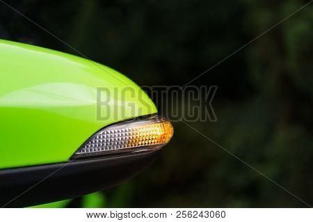 Turn Signal Or Blinker Lit In Mirror Of A Modern Green Car.