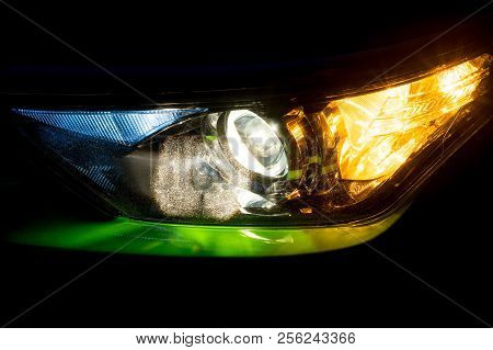 Front Headlight On A Modern Green Car At Night. Low Beam And Turn Signal Or Blinker Lit.