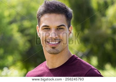 Portrait of young latin man with toothy smile looking at camera. Happy handsome guy in casual at park in a summer day. Closeup face of stylish man relaxing outdoor.