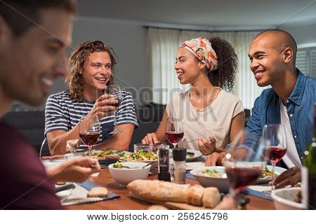 Happy cheerful multiethnic couple enjoying meal with friends at home. Happy guys and girls enjoying lunch together indoor. Four friends eating together with red wine sitting around the table.