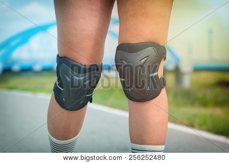 Woman rollerskater wearing knee protector pads on her leg poster