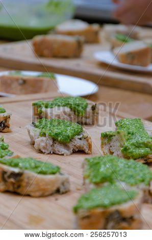 Fresh Baked Bread And Basil Pesto On Brown Wooden Table
