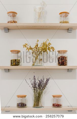 Close-up View Of Various Ingredients In Glass Containers On Wooden Shelves With Some Dried Shrubs